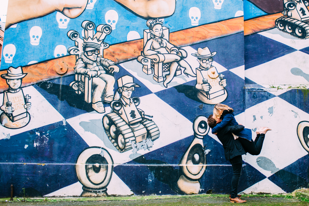 couple kissing for engagement shoot next to graffiti in Brighton