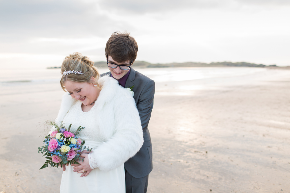 bride and groom laughing on Newborough beach