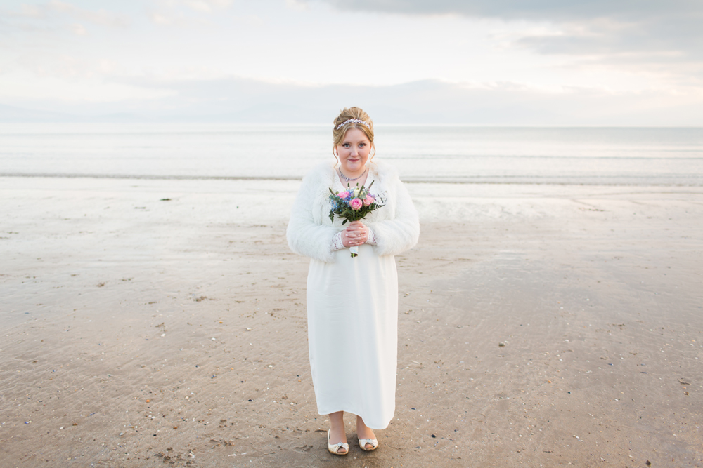 bride with pink bouquet smiling on the beach