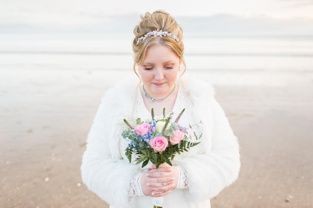 close up bride on Newborough beach holding her bouquet