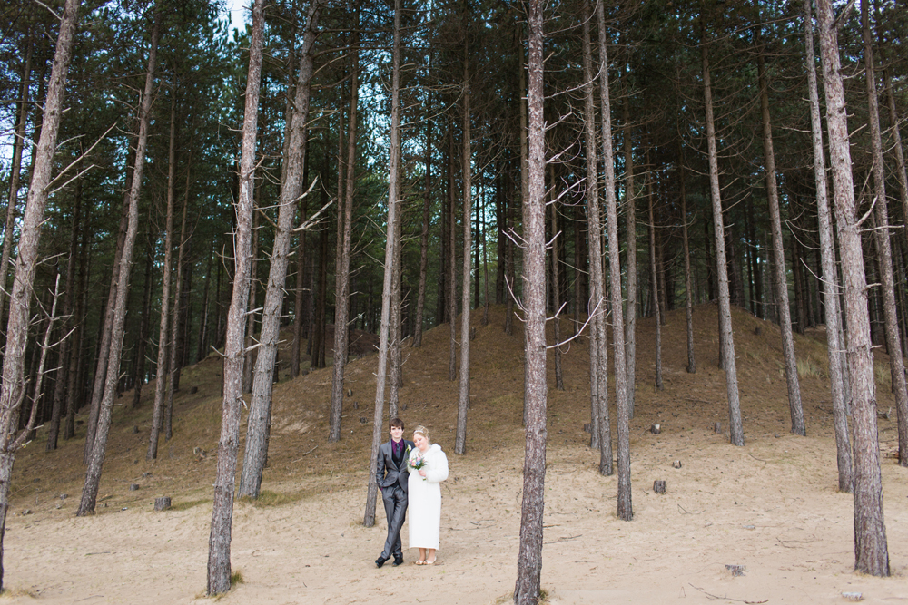 bride and groom standing amongst tall trees