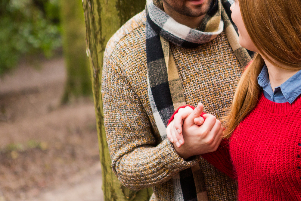 Holding hands on engagement shoot in Stanmer Park