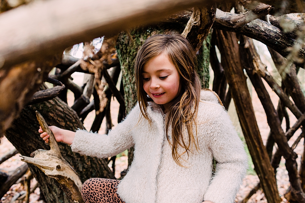 Girl hiding in a den in Ditchling common